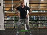 trainer doing lateral lunges with resistance band