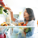 woman holding food and looking through refrigerator